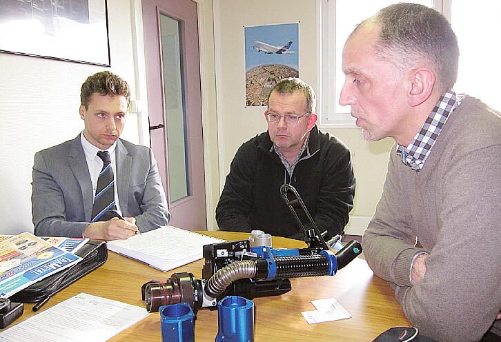 De gauche à droite MM.Smagghe, Gillet et Monier avec une perceuse à rivets sur la table.